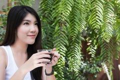 La mujer asiática se sienta en el café al aire libre adulto femenino joven con natural Fotos de archivo libres de regalías