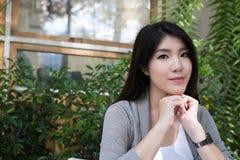 La mujer asiática se sienta en el café al aire libre adulto femenino joven con natural Imagen de archivo libre de regalías