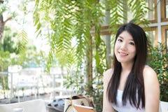 La mujer asiática se sienta en el café al aire libre control adulto femenino joven digital Fotos de archivo libres de regalías
