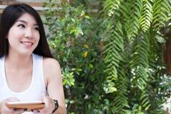 La mujer asiática se sienta en el café al aire libre control adulto femenino joven digital Imagen de archivo libre de regalías