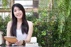 La mujer asiática se sienta en el café al aire libre control adulto femenino joven digital Imagenes de archivo