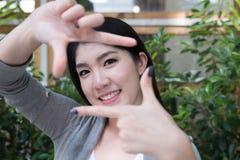 La mujer asiática se sienta en el café al aire libre marco de fabricación adulto femenino joven Foto de archivo libre de regalías