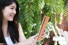 La mujer asiática se sienta en el café al aire libre uso adulto femenino joven digital Imágenes de archivo libres de regalías