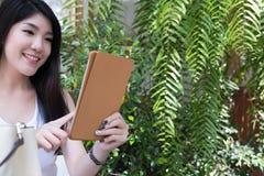 La mujer asiática se sienta en el café al aire libre uso adulto femenino joven digital Imagen de archivo libre de regalías