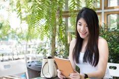 La mujer asiática se sienta en el café al aire libre uso adulto femenino joven digital Foto de archivo