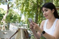 La mujer asiática se sienta en el café al aire libre uso adulto femenino joven p móvil Imágenes de archivo libres de regalías