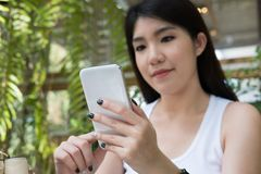La mujer asiática se sienta en el café al aire libre uso adulto femenino joven p móvil Foto de archivo
