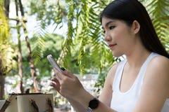 La mujer asiática se sienta en el café al aire libre uso adulto femenino joven p móvil Foto de archivo libre de regalías