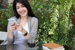 La mujer asiática se sienta en el café al aire libre uso adulto femenino joven p móvil Imagen de archivo