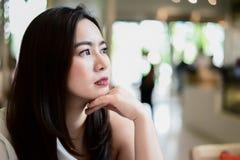 La mujer asiática se sienta en la silla en restaurante del fondo de la falta de definición Ella está esperando alguien Fotos de archivo