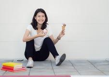 La mujer asiática se sienta y se relaja con helado foto de archivo