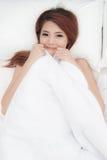 La mujer asiática sonriente de la cara apenas despierta en cama Imagen de archivo