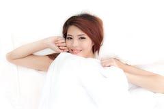 La mujer asiática sonriente de la cara apenas despierta en cama Foto de archivo libre de regalías