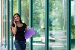 La mujer asiática sonriente habla en el teléfono celular mientras que camina al lado de gl Fotos de archivo