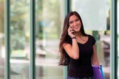 La mujer asiática sonriente habla en el teléfono celular mientras que camina al lado de gl Imagen de archivo