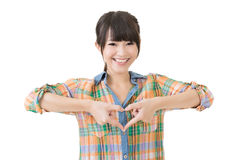 La mujer asiática sonriente hace forma del corazón Imagen de archivo