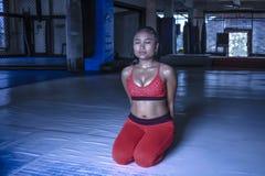 La mujer asiática sudorosa agotada en deporte viste la respiración y el stre Imagen de archivo