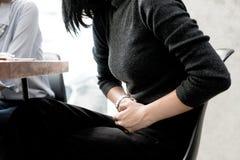La mujer asiática tiene dolor de estómago mientras que ella reunión con su amigo adentro Foto de archivo libre de regalías