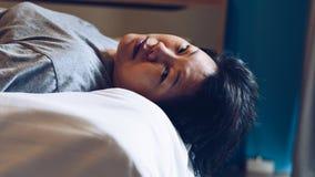 La mujer asiática toma una siesta o duerme en cama en dormitorio Fotografía de archivo