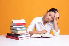 La mujer asi?tica joven agotada ley? un libro con los libros en la tabla fotografía de archivo libre de regalías
