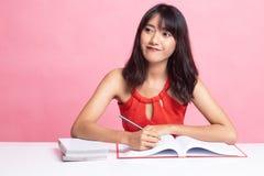 La mujer asi?tica joven ley? un libro con los libros en la tabla fotos de archivo libres de regalías