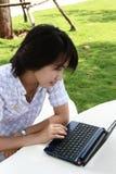 La mujer asiática atractiva está al aire libre con la computadora portátil Imagenes de archivo