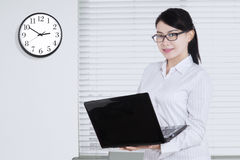La mujer asiática celebra el ordenador portátil en el lugar de trabajo Imágenes de archivo libres de regalías