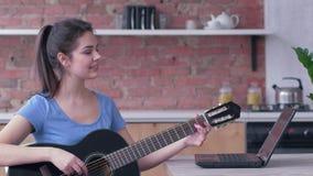La mujer asombrosa del músico que aprende la guitarra del juego utiliza el ordenador portátil con la enseñanza video en línea almacen de video
