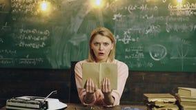 La mujer asombrosa lee un libro en la sala de clase contra fondo de la pizarra verde El estudiante chocado sostiene el libro metrajes