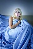 La mujer asustó en cama fotos de archivo