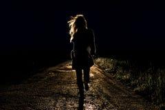 La mujer asustada los jóvenes solos en un camino vacío de la noche corre lejos teniendo en cuenta las linternas de su coche imagen de archivo