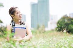La mujer atenta agradable joven que se sienta en hierba verde y el abrazo reservan Fotografía de archivo