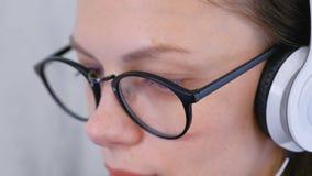La mujer atenta joven en vidrios y auriculares está trabajando, primer de la cara almacen de metraje de vídeo