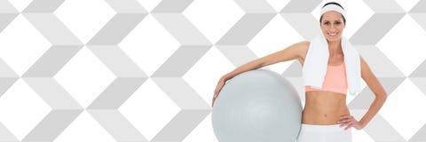 La mujer atlética apta con el diamante forma sostener la bola del ejercicio Imagen de archivo
