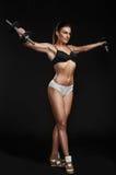 La mujer atlética brutal que bombea para arriba muscles con pesas de gimnasia Fotos de archivo libres de regalías