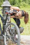 La mujer atlética con el agua potable de la bicicleta después del ejercicio, aventaja imagen de archivo libre de regalías