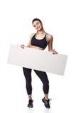 La mujer atlética de la aptitud con deporte helthy del espacio en blanco del tablero de la muestra aisló la ropa blanca del negro Fotografía de archivo