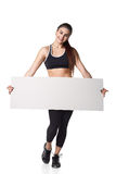 La mujer atlética de la aptitud con deporte helthy del espacio en blanco del tablero de la muestra aisló la ropa blanca del negro Imagen de archivo libre de regalías