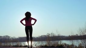 La mujer atlética entra para los deportes en la orilla del río en la salida del sol C?mara lenta almacen de video