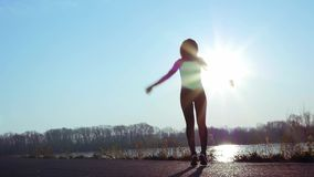La mujer atlética entra para los deportes en la orilla del río en la salida del sol C?mara lenta metrajes