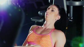 La mujer atlética entrenó a los músculos de las piernas en el simulador de los deportes almacen de video