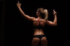 La mujer atlética hermosa en paños deportivos está presentando, está llevando a cabo las manos ascendentes y está mostrando su cu Imagenes de archivo