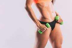 La mujer atlética brutal que bombea para arriba muscles con pesas de gimnasia Imagenes de archivo
