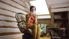 La mujer atractiva adulta en vidrios bebe el café en ático almacen de metraje de vídeo