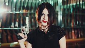 La mujer atractiva apunta un arma metrajes
