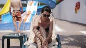 La mujer atractiva atractiva encendido sunbed cerca de la piscina que aplicaba la loción de bloque de sol en su cuerpo metrajes