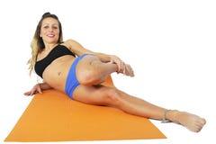 La mujer atractiva atractiva joven del ajuste en el gimnasio que hace ejercicio de la yoga y que estira en la estera en la medita Imagenes de archivo