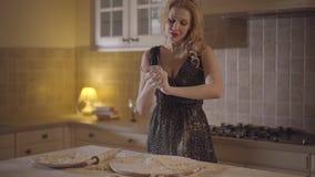 La mujer atractiva bonita en el vestido negro manchado con pasta de mezcla de la harina en manos y fuertemente lanza la pasta en metrajes