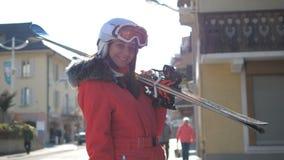 La mujer atractiva coloca las casas cercanas que la detienen esquí en declive antes de esquiar fotos de archivo
