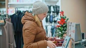 La mujer atractiva compra ropa, sostiene el dinero a disposición, oficina de los cajeros Centro comercial almacen de metraje de vídeo